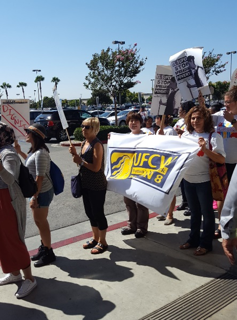 Ryuko Kiruta and Julia Quinonez carry the United Food and Commercial Workers' banner at the local action event.